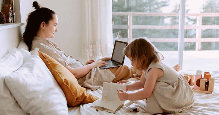 Mutter arbeitet am Laptop im Bett, Kind spielt daneben